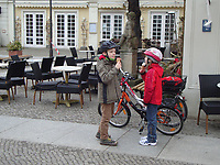 Boy and girl eating ice-cream near bicycles in the Potsdam