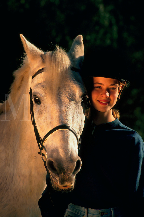 Portrait of a smiling young girl in a riding helmet posing next to a white horse.