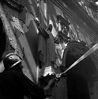 Eglise de Lalande, chemin de l'Eglise-de-Lalande. 20 juin 1961. Plan rapproché d'un pompier en train d'éteindre le feu : au 1er plan pompier avec casque de profil tient une lance à eau ; en arrière plan statue de Sainte-Thérèse. Cliché pris pendant l'incendie qui a ravagé l'église de Lalande.