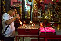 Sin Sze Si Ya Taoist Temple, Chinatown, Kuala Lumpur, Malaysia.  Worshiper Lighting Joss Sticks (incense Sticks).  Oldest Taoist temple in Kuala Lumpur (1864).