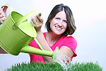 A woman using a watering can to water grass focus on the water