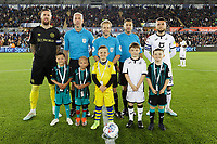 Pontus Jansson of Brentford (L), Matt Grimes of Swansea City (R) and referee Gavin Ward (C) with children mascots during the Sky Bet Championship match between Swansea City and Brentford at the Liberty Stadium, Swansea, Wales, UK. Tuesday 22 October 2019