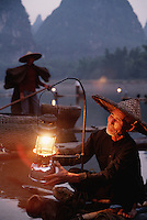 Detail image of a Li River Cormorant fishermen on a bamboo raft lighting a lantern at dusk. Guilin Guangxi, China..