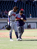 Ronald Acuna of the Peoria Javelinas is being attended by trainer Nick Kuchwara after being hit on the wrist by a pitch in the third inning of an Arizona Fall League game against the Mesa Solar Sox at Sloan Park on October 12, 2017 in Mesa, Arizona (Bill Mitchell)
