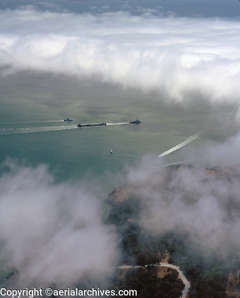 aerial photograph of tug boat towing a barge on a foggy day, San Francisco Bay