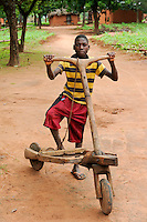 ANGOLA Kwanza Sul, village Cassombo, boy with wooden scooter to transport goods / ANGOLA Kwanza Sul, Dorf Cassombo, Junge mit Holzroller zum Lastentransport