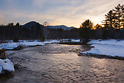 Sunset from along the Swift River during the winter months. This river travels along side of the Kancamagus Highway (route 112) which is one of New England's scenic byways in the White Mountains, New Hampshire USA. This area was part of the Swift River Railroad, which was an logging railroad in operation from 1906 - 1916. Mount Passaconaway is off in the distance