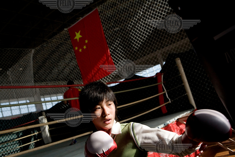 """A young female boxer training at the Qingdao City Sports School, one of the country's top breeding grounds for Olympic athletes. Principal Qiao Xiangdong credits the Beijing 2008 Olympic Games for spurring the local government to build a USD 42 million new campus for the academy's 600 students. """"Before, some parents were worried about sending their kids to sports schools because they thought their children would have to eat too much bitterness,"""" Qiao says, using the Chinese term for enduring hardship. """"But the Olympic Games have made people willing to contribute to the nation's glory."""""""