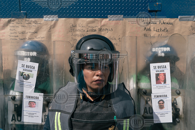 A police officer wearing riot gear stands in front of other police officers holding riot shields on which protestors have attached leaflets displaying the images of men accused of crimes against women. Behind them on a wall is a list of the names of victims of femicide. The annual International Women's Day demonstrationintensified and turned into a bigger movementagainst gender-based violenceamid an increase in killings of women and girls.