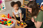 Education preschool 2-3 year olds early intervention play therapy one to one pull out from classroom female therapist working with girl