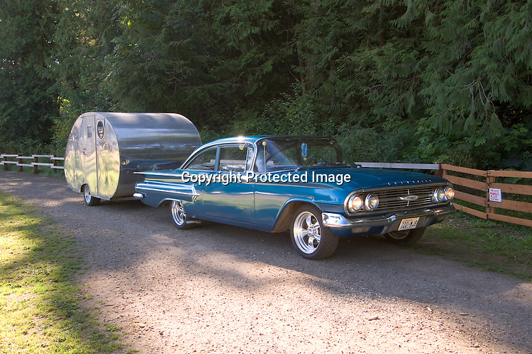 1960 blue green Chevy Bel Air pulling a 1938 West Coast Body Builders vintage travel trailer with an aluminum finish.