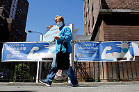 """NEW YORK - NEW YORK - APRIL 13: A woman walks near a Covid-19 Vaccination Center on April 13, 2021 in New York. U.S. Federal health officials called for a pause in the use of the Johnson & Johnson Coronavirus vaccine after """"extremely rare"""" cases of blood clots. (Photo by John Smith/VIEWpress)"""