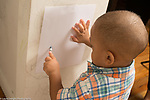 21 month old toddler boy scribbling on paper on wall with crayon, after scribbling on wall