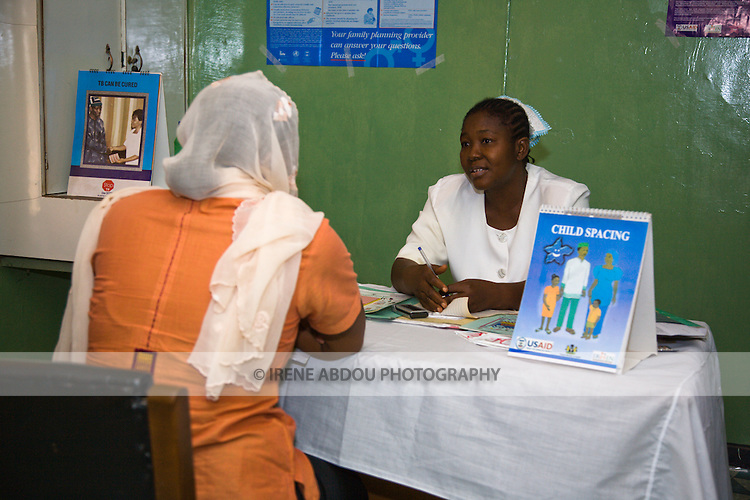 A U.S. Agency for International Development (USAID) employee talks to a health official at the Bukavu Barracks public clinic in Kano, Nigeria.  A child spacing flipchart, designed by Nigeria's largest indigenous non-profit organization, the Society for Family Health, is prominently displayed on the desk.