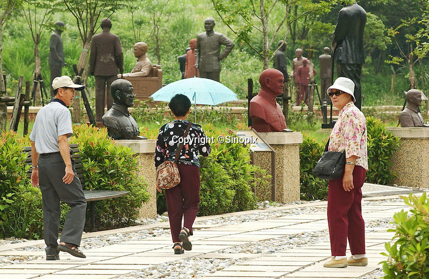 Taiwanese tourists at the Tzuhu visitors centre, aka Tzuhu Presidential Burial Place, at the mausoleum of the former leader. The centre has hundreds of such statues collected from around the country..19 Jun 2007