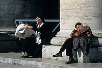 Nun seated reading a newspaper while a man is taking a nap in Saint Peter's Square, Vatican City, Rome, Italy.