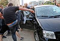 Pictured: Thessaloniki mayor Yiannis Boutaris is moved to safety while being attacked in northern Greece. <br /> Re: Thessaloniki's mayor, Yiannis Boutaris, has been attacked during an event commemorating the first world war massacre of Black Sea Greeks by Turks.<br /> He was rushed to hospital with head, back and leg injuries. <br /> Footage from the scene shows the mayor being heckled before the assailants hurled bottles at him and kicked him in the head and legs. As he is escorted into his car, some of the attackers attempt to smash the vehicle's windows.<br /> Police have arrested two people.