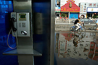Public phone booth with people riding bicycles in the background, Datong, Shanxi, China.