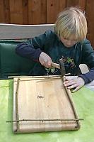 Kinder basteln ein Fensterbild mit Blüten, Junge nagelt Holzrahmen aus Haselbaumästen zusammen