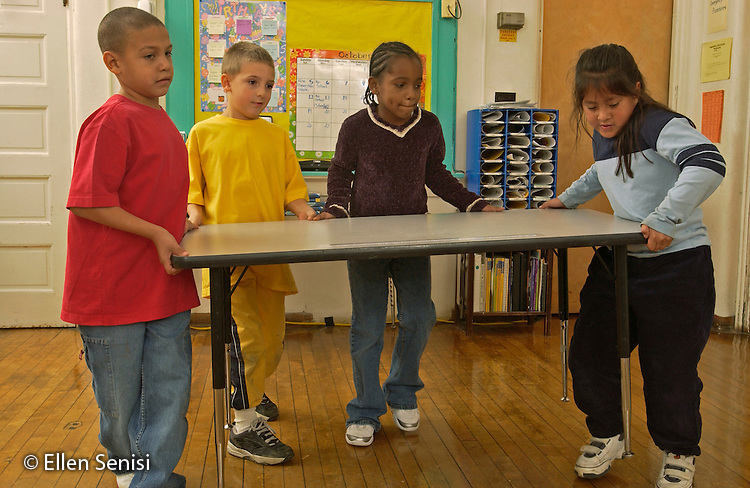MR / Schenectady, NY.Yates Arts-in-Education Magnet School, Grade 2.Arts-Themed Urban Elementary School.Students work together to lift, carry, and move heavy table in classroom..MR: g2c.© Ellen B. Senisi