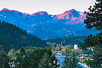 first light of day on peaks in Rocky Mountain National Park above town of Estes Park, autumn morning in Colorado, USA