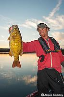 Man hoisting smallmouth bass Evening bass fishing