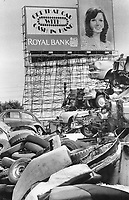 The end of the road; Where will it all end; those long files of cars on the expressways? Many of them wind up at the American Auto Wreckers yard on Parliament St.; where about 800 cars are heaped up; many of them late models. To complete the circle; though; a big billboard encourages car owners to replace the scrapped cars right away.<br /> <br /> Photo : Boris Spremo - Toronto Star archives - AQP