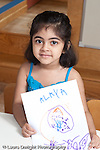 Education Preschool 3-5 year olds portrait of girl with her drawing with her name written on top in marker proud of drawing art activity vertical