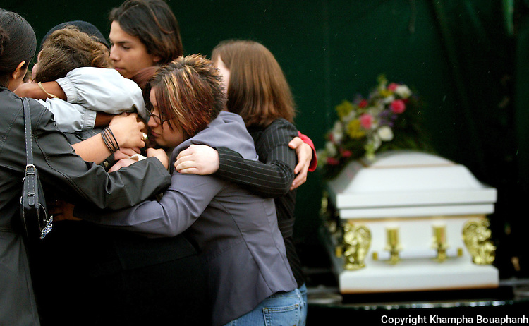 Friends and family comfort each other at the burial of 14-year-old Lan Bui of Haltom City, Texas on February 12, 2005.  Bui was killed earlier in the week and her body found gagged and bound at a playground near her home.  (photo by Khampha Bouaphanh)