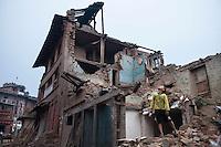 Samir, 9, stands on his destroyed house in Bhaktapur, near Kathmandu, Nepal. May 7, 2015