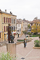 The new statue of Cyrano de Bergerac on the main town square in Bergerac, unusual in that it is painted in colour and standing on a stainless steel pedestal. A woman walking on the square. on Place Pelissiere Square Bergerac Dordogne France