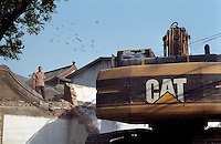 A migrant worker stands on a roof of an old house looking on a Caterpillar buildozer to demolish the old house of a central Hutong in Beijing, China..
