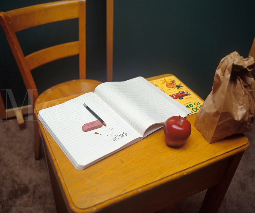 A grade school desk with a notebook, lunch and apple on top.
