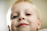 face of young boy smiling with blue eyes and happy