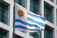 The Uruguay flag, blue and red stripes and a sun on white background, against a background of a modern office building on the Plaza Independencia Independence Square Montevideo, Uruguay, South America