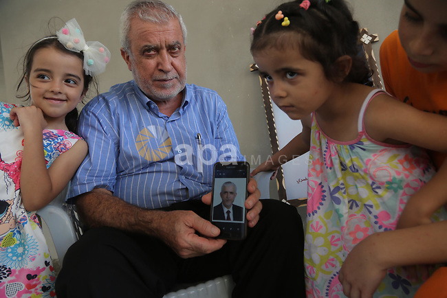 Abd al-Majid al-Khudari, brother of the prisoner Mohammad al-Khudari who is detained in Saudi Jails, looks on the mobile at his home in Gaza city on August 09, 2021. The Saudi court issued verdicts against 69 Palestinians with sentences ranging from 3-22 years without allowing relatives of detainees to attend the trial.<br />  Photo by Ashraf Amra