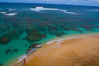 Young woman surfer exits crystal clear waters of Hideaways Beach, a snorkeling heaven in Princeville, North Shore of Kauai