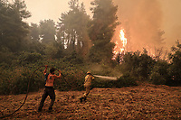 Pictured: A firefighter and a volunteer fight the flames with a hose at the village of Pefki in northern Evia siland, Greece. Sunday 08 August 2021<br /> Re: Forest fire in northern Evia, Greece.