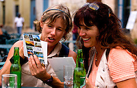 Tourist girl friends relax with drinks and look at postcards and have fun