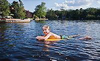 Little boy floating on a body board in a public lake