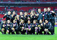August 09, 2012: USA women's soccer team members Hope Solo, Heather Mitts, Christie Rampone, Becky Sauerbrunn, Kelley O'Hara, Amy Le Peilbet, Shannon Boxx, Amy Rodriguez, Heather O'Reilly, Carli Lloyd,  Sydney Leroux, Lauren Cheney, Alex Morgan, Abby Wambach, Megan Rapinoe, Rachel Buehler, Tobin Heath,  Nicole Barnhart pose for a photograph at the conclusion of award ceremony during Football Final match at the Wembley Stadium on day thirteen in Wembley, England. USA defeat Japan 2-1 to win it's third consecutive Olympic gold medal in women's soccer. ..