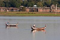 Myanmar, Burma, Mandalay.  Taungthaman Lake.  Two Boats in Afternoon Sun, U Bein Bridge in Background.