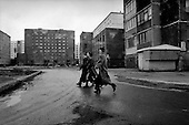 Norilsk, Russia  .May-June 1997.Three young women walk the streets of Norilsk in style as the harsh living conditions of the northern Siberian permafrost surrounds them. The city was first established as a gulag. It now mines a vast reserve of nickel..