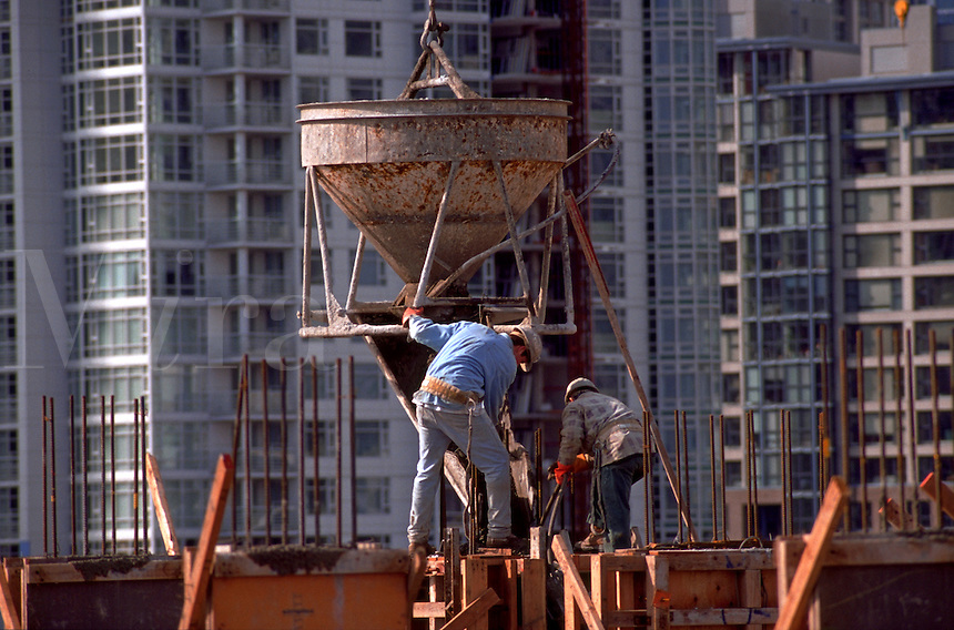 Workers pouring cement at a construction site.