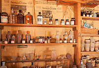 Chemical bottles and other supplies in the assay building at Cerro Gordo, a late 19th century mining community in the Inyo Mountains near Keeler, California. Newspapers on the wall are dated August 1957.