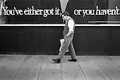 You've either got it or you haven't.  A man walks past an advertising hoarding on the Harrow Road, West London (1983).