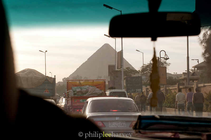 Approaching one of the Giza Pyramids along a busy main road, Giza, Egypt