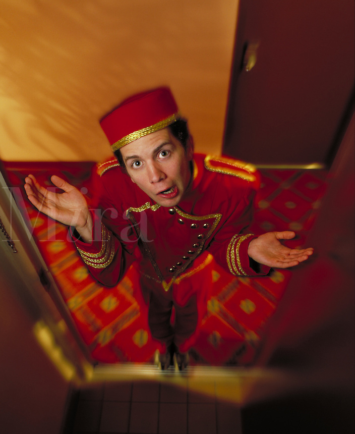 """Hotel bellhop throwing up his hands in exasperation, as if he is saying """"""""I don't know where your luggage is"""""""". Billboard and broadcast must be negotiated, due to talent agreement. Bellhop. United States Hotel."""