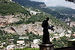 A statue of a priest helps the view in the hills above Positano town and the Mediterranean Sea, on the Amalfi Coast in the Gulf of Naples