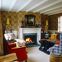 The cosy living room is papered in William Yeoward's 'Hortense Gold' and the furniture is upholstered in a variety of his fabrics